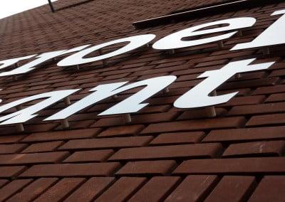 Afstandhouders freesteksten logo op bakstenen muur